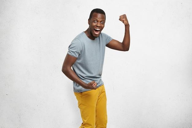 Tiro al coperto di bello giovane studente afroamericano fortunato eccitato che esclama per l'eccitazione