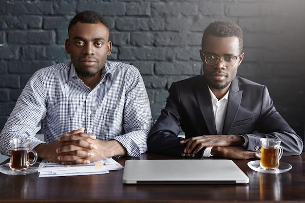 Tiro al coperto di due uomini d'affari di successo che hanno riunione nell'interiore dell'ufficio moderno