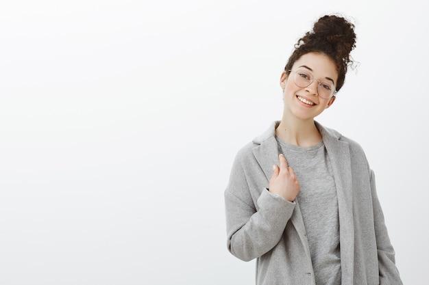 Tiro al coperto di elegante donna dai capelli ricci attraente indipendente in occhiali alla moda e cappotto grigio, toccando i vestiti
