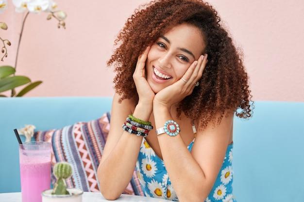 Tiro al coperto di felice razza mista femmina con capelli ricci e felice espressione, indossa abiti estivi, si siede su un comodo divano, beve frullato fresco