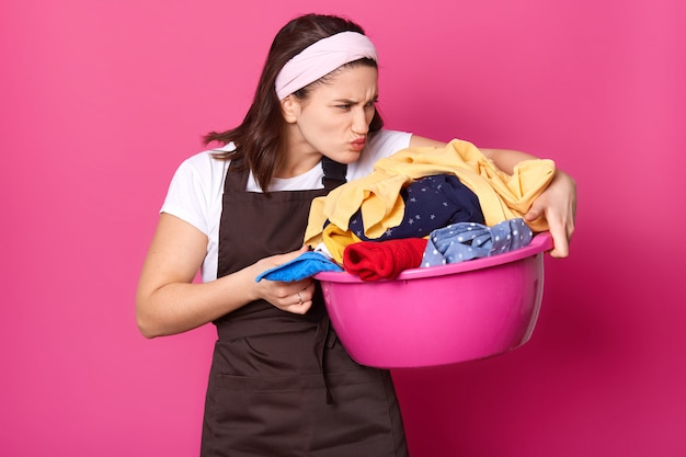 Tiro al coperto di giovane casalinga stanca, fare le faccende di casa, odorare i vestiti sporchi, andare a lavarli, avere un'espressione disgustosa del viso, odia il processo di lavaggio. concetto di faccende domestiche e domestiche.