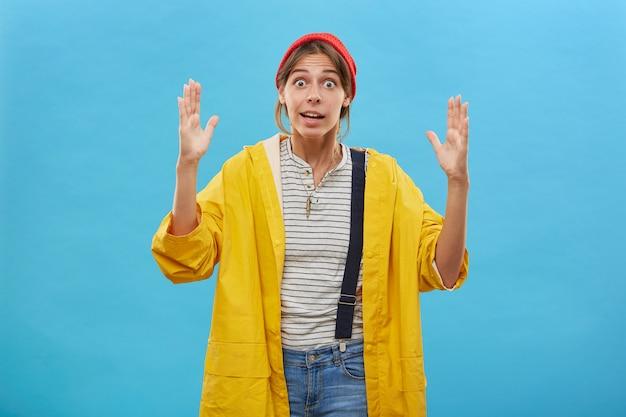 Tiro al coperto di operaio femminile sorpreso che mostra le dimensioni bella femmina che dimostra le dimensioni di qualcosa di grande o enorme con le mani. donna stupita che gesturing sopra la parete blu