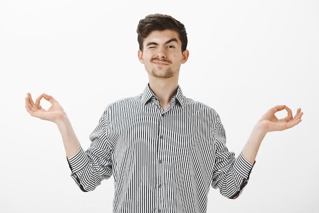 Tiro al coperto di un ragazzo gentile e spensierato con i baffi in camicia, mani aperte in un gesto zen, sbirciare con un occhio e sorridere mentre guardano gli studenti durante la pratica dello yoga o della meditazione