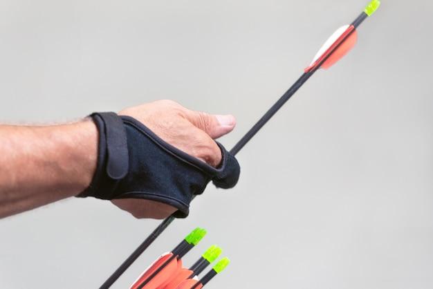 Tiro con l'arco. esercizio con l'arco con l'arco. sport, concetto di ricreazione. lo sportivo sta preparando la freccia per il tiro.