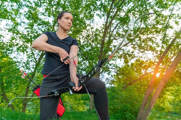 Tiro con la freccia da un arco in natura, tiro con l'arco sportivo. copia spazio