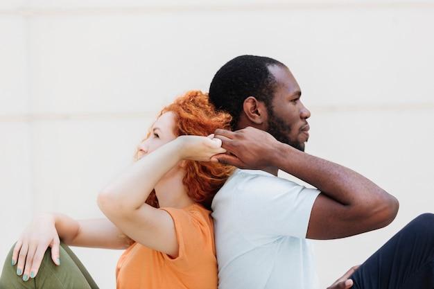 Tiro medio di coppia interrazziale schiena contro schiena tenendosi per mano