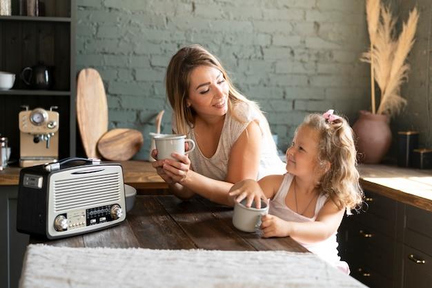 Tiro medio madre e figlia tenendo tazze