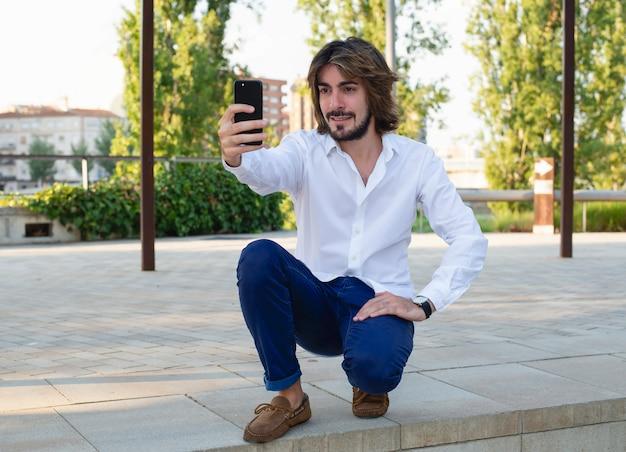 Tiro orizzontale di attraente giovane con capelli lunghi, barba, camicia bianca, pantaloni blu fa un selfie con il suo smartphone.