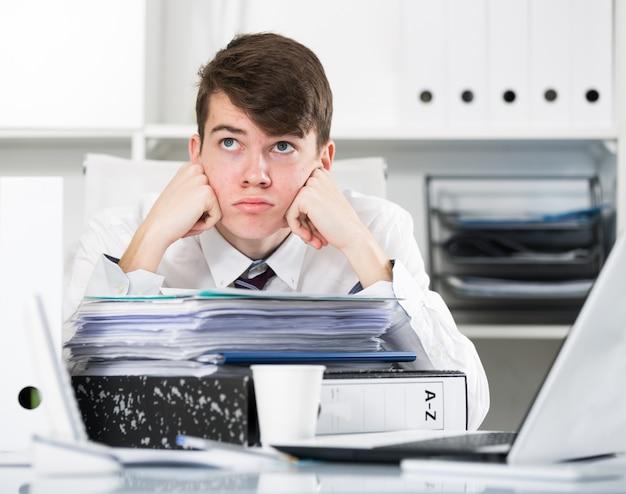 Tirocinante vicino alla pila di documenti e tazza