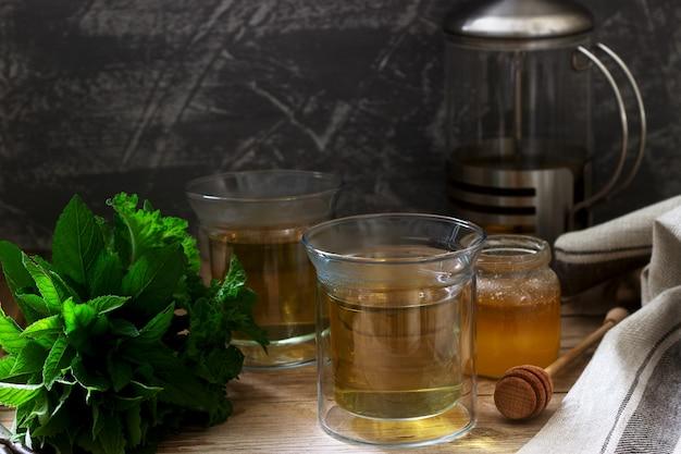 Tisana a base di menta e melissa con miele in tazze di vetro. stile rustico.