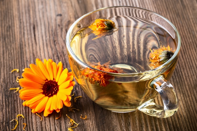Tisana alla calendula (calendula) in una tazza di vetro trasparente con fiori secchi