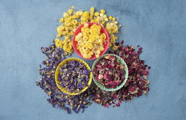 Tisana aromatica alla camomilla, rosa e lavanda sfusa sul tavolo di legno blu