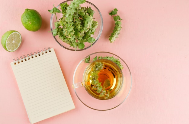 Tisana con erbe, lime, taccuino in una tazza di vetro su rosa, vista dall'alto.