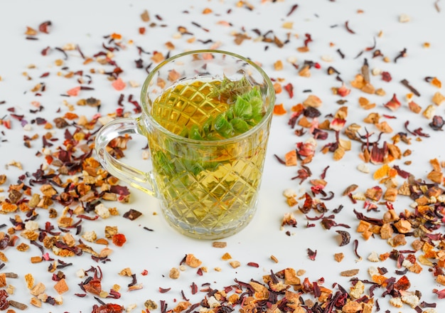 Tisana con le erbe secche in una tazza di vetro sulla vista bianca e dell'angolo alto.