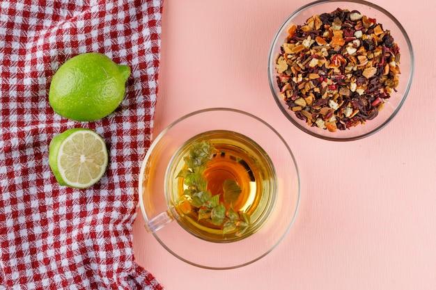 Tisana con lime, erbe essiccate in una tazza di vetro su un asciugamano rosa e da cucina, piatto disteso.