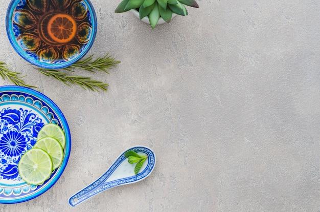 Tisana fatta in casa a base di foglie di menta; fette di limone; rosmarino su sfondo concreto