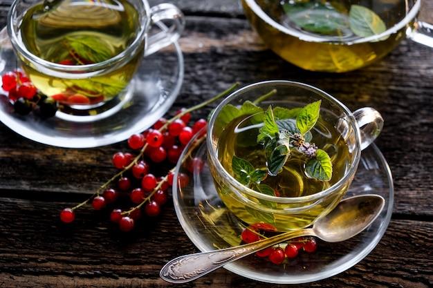 Tisana verde con bacche in tazza di vetro sulla tavola di legno