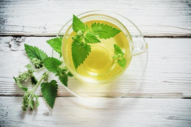 Tisana verde della melissa in tazza di vetro sulla tavola di legno