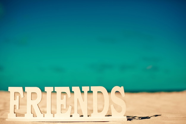 Titolo amici sulla sabbia bianca dietro il cielo blu vicino oceano