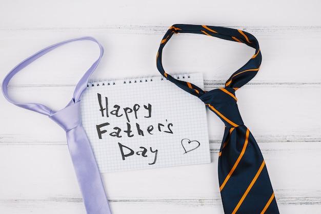 Titolo del giorno di padri felice sul foglio vicino a cravatte