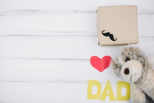 Titolo di carta cuore rosso e papà vicino a giocattolo e scatola