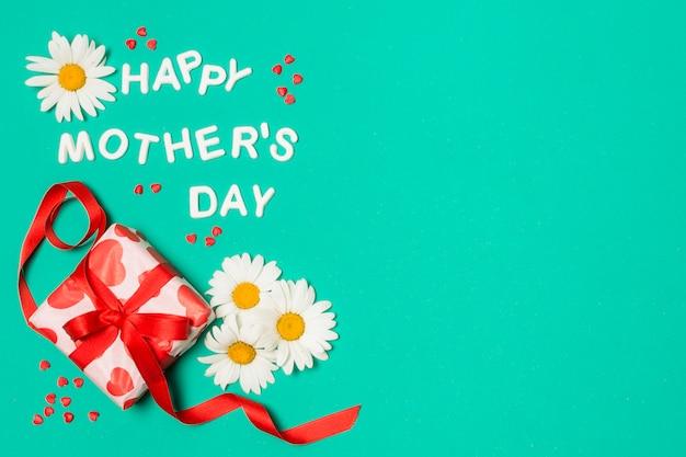 Titolo di giorno di madri felice vicino a fiori bianchi e scatola regalo
