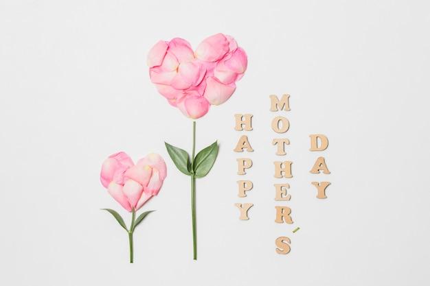 Titolo di giorno di madri felice vicino alla fioritura rosa a forma di cuore