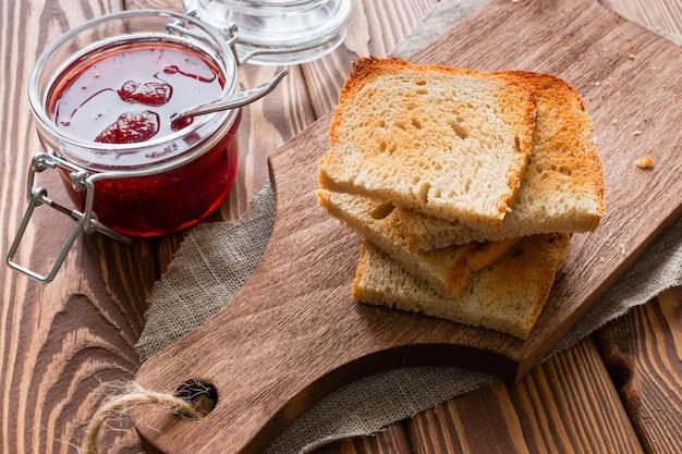 Toast accatastati accanto a un barattolo di marmellata