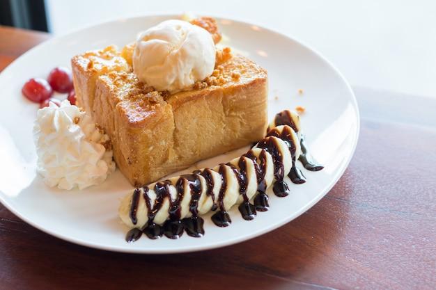 Toast al miele con gelato alla vaniglia, panna montata e sciroppo di cioccolato. servito con banana, uva e mela