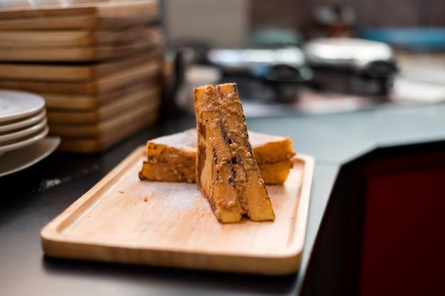 Toast alla francese con burro di arachidi sul piatto di legno