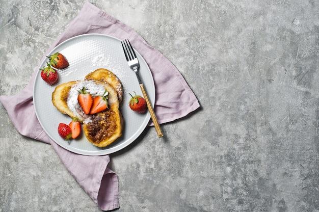 Toast alla francese con fragole e sciroppo d'acero su un piatto grigio.