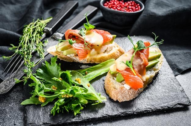 Toast con avocado e salmone affumicato. sfondo nero. vista dall'alto