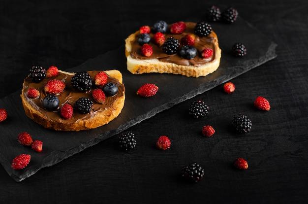 Toast con burro di noci al cioccolato con frutti di bosco freschi su sfondo scuro