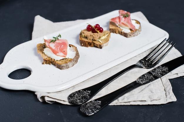 Toast con parma, salame e patè d'oca su un tagliere bianco