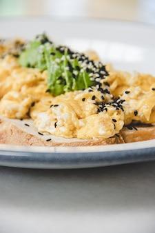 Toast con uova strapazzate su un piatto bianco. avvicinamento.