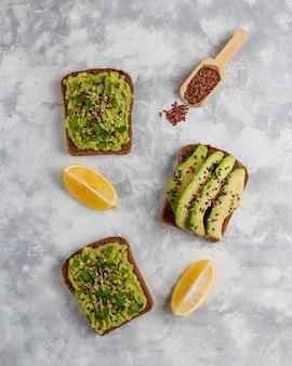Toast di avocado aperto con fette di avocado, limone, semi di lino, semi di sesamo, fette di pane nero, vista dall'alto