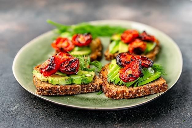 Toast di avocado con pomodori arrostiti in un piatto
