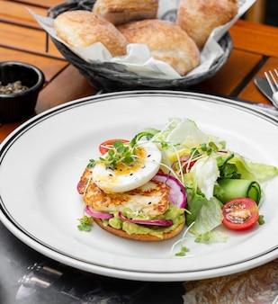 Toast di avocado condito con raddish, syrniki e uovo sodo servito con insalata fresca