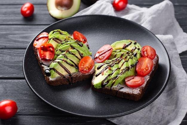 Toast di avocado per colazione sul piatto con pomodori e salsa