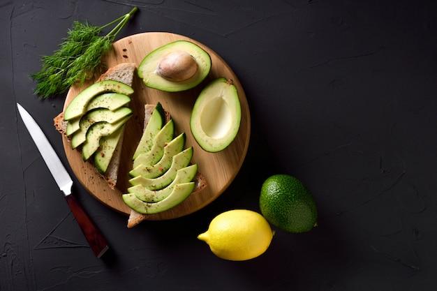 Toast di avocado splendidamente placcato con condimenti dall'aspetto delizioso sul tavolo di legno e sfondo scuro. su un tagliere di legno. avocado a fette di pane tostato con spezie