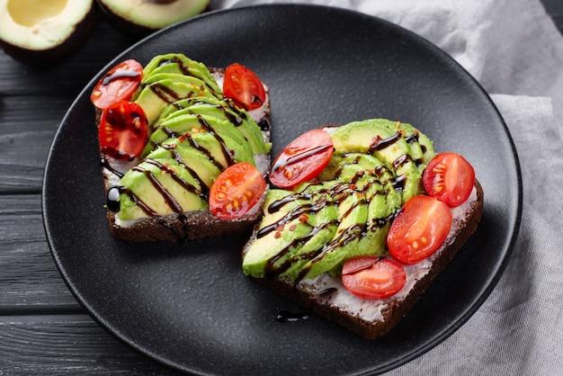 Toast di avocado sul piatto con pomodori e salsa