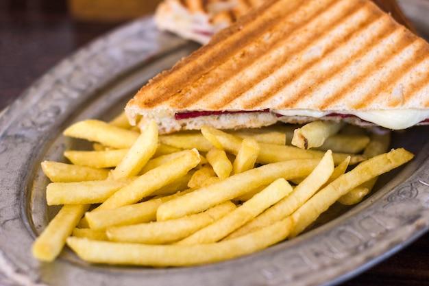 Toast triangolare con formaggio e prosciutto su un vecchio piatto di latta con patatine fritte