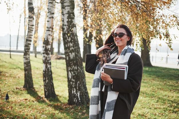 Tocca i capelli con una mano. il giovane castana sorridente in occhiali da sole sta nel parco vicino agli alberi e tiene il blocco note