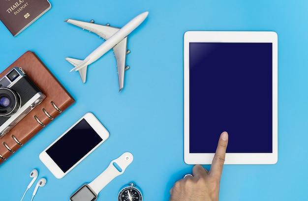 Toccando lo schermo del tablet vuoto con il concetto di oggetto di viaggio