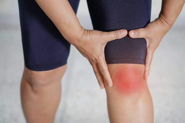 Tocco e sensazione paziente di signora di mezza età asiatica dolore al ginocchio.