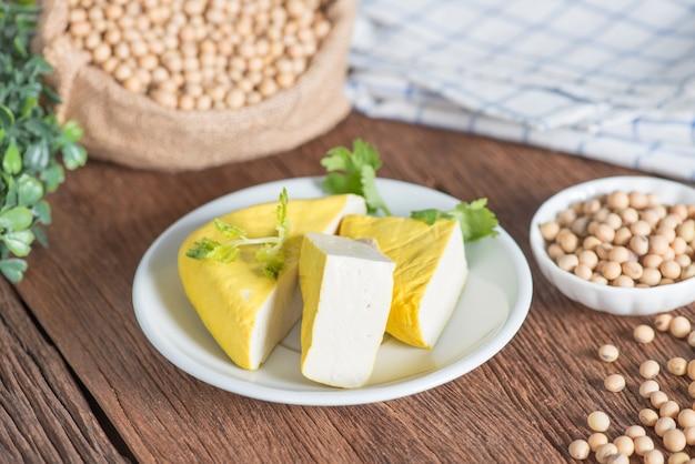 Tofu giallo affettato sul piatto con fagioli di soia.