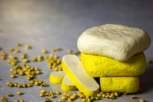 Tofu impilabile sul tavolo e semi di soia sparsi sul tavolo.