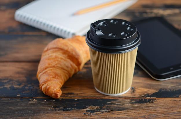 Togliere la tazza di caffè con cornetto sul tavolo di legno.