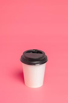 Togliere la tazza di caffè su sfondo di carta colorata