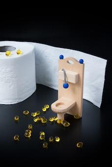 Toilette, capsule e carta di legno del giocattolo sul nero